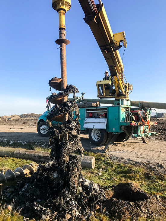 Augering a hole through garbage at the Vancouver Landfill. We installed 12 pcs 45' poles and 2 push braces on this project.