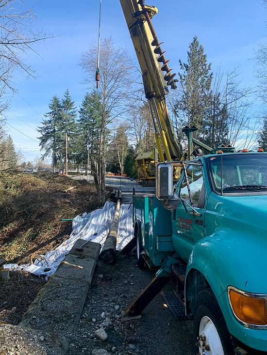 Using our digger derrick to place a 70' pole for a temporary bridge in Langley